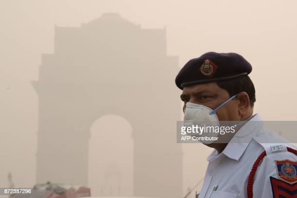 This photo taken on November 9 2017 shows an Indian policeman wearing a protection mask as he works near India Gate amid heavy smog in New Delhi...