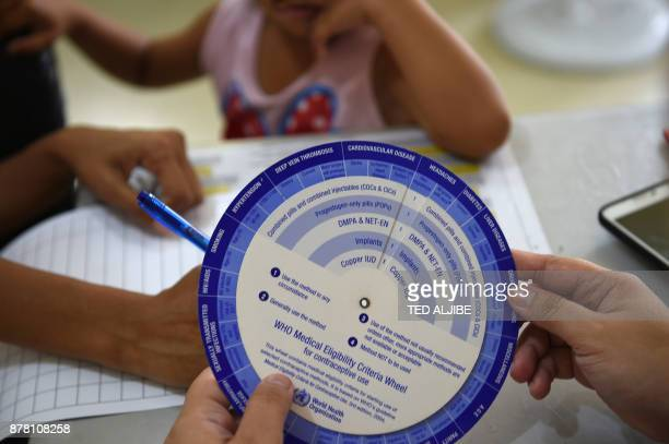 This photo taken on October 10 2017 shows a mother filling up forms as a medical worker looks at a contraceptive user guide at a clinic run by the...