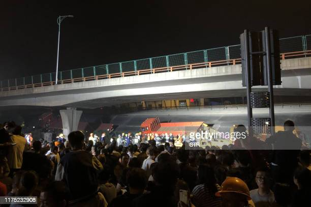 This photo taken on October 10, 2019 shows a crowd watching workers at the site of a highway overpass collapse in Wuxi, China's eastern Jiangsu...