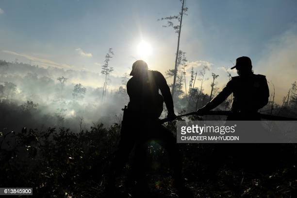 This photo taken on October 10 shows rangers extinguishing a fire in Seulawah Aceh Besar district in Aceh province after the fire scorched hectares...
