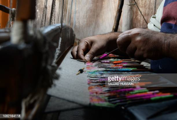 This photo taken on October 11 shows a Kashmiri artisan working on a woven Kani or Jamewar shawl at his workshop on the outskirts of Srinagar Some...