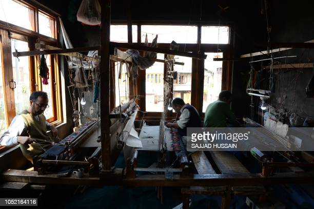 This photo taken on October 11 shows Kashmiri artisans working on a woven Kani or Jamewar shawl at their workshop on the outskirts of Srinagar Some...