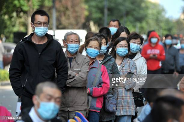 This photo taken on October 12, 2020 shows residents lining up to be tested for the COVID-19 coronavirus, as part of a mass testing program following...