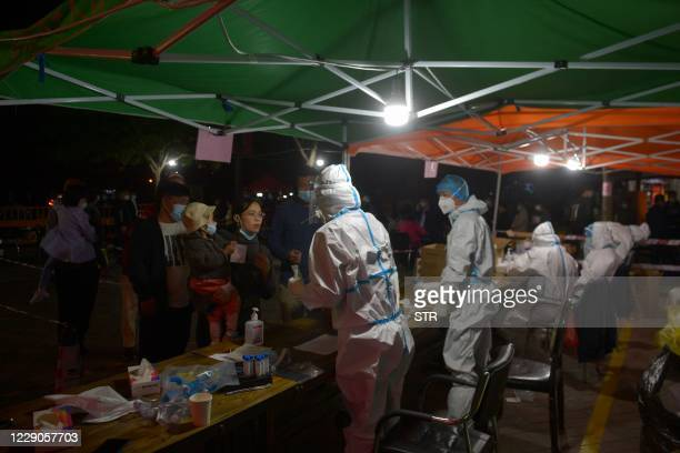 This photo taken on October 13, 2020 shows residents waiting to be tested for the COVID-19 coronavirus as part of a mass testing program following a...