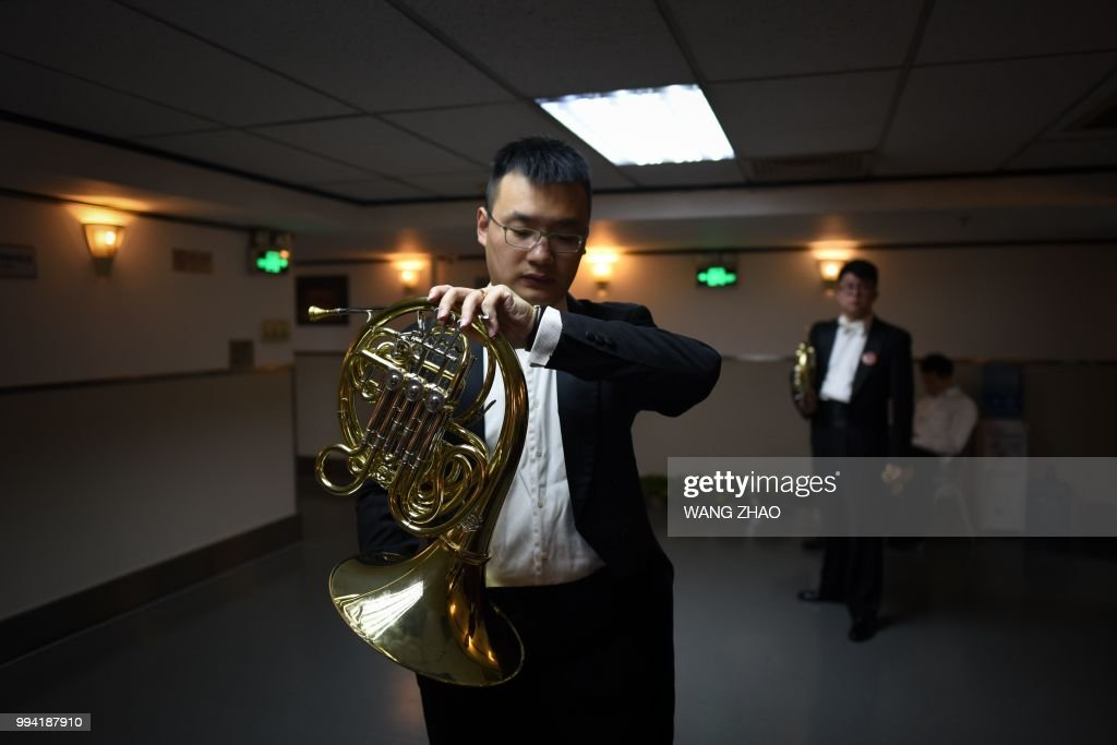 This photo taken on October 14, 2017 shows a musician looking at his watch as he prepares backstage before a symphonic concert at a theatre in Beijing. - After long relying on Western conductors, a growing number of symphony orchestras around China are now entrusting the baton to a fresh generation of Chinese leaders. (Photo by WANG Zhao / AFP) / TO GO WITH China-music, FEATURE by Julien Girault