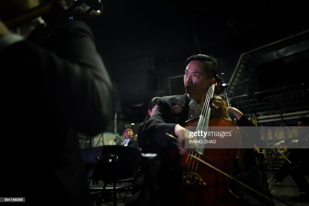 This photo taken on October 14, 2017 shows a musician preparing backstage before a symphonic concert at a theatre in Beijing. - After long relying on Western conductors, a growing number of symphony orchestras around China are now entrusting the baton to a fresh generation of Chinese leaders. (Photo by WANG Zhao / AFP) / TO GO WITH China-music, FEATURE by Julien Girault