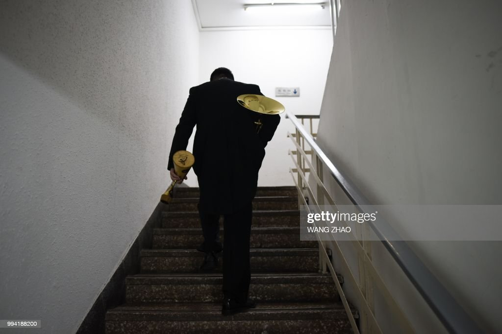 This photo taken on October 14, 2017 shows a musician walking backstage before a symphonic concert at a theatre in Beijing. - After long relying on Western conductors, a growing number of symphony orchestras around China are now entrusting the baton to a fresh generation of Chinese leaders. (Photo by WANG Zhao / AFP) / TO GO WITH China-music, FEATURE by Julien Girault