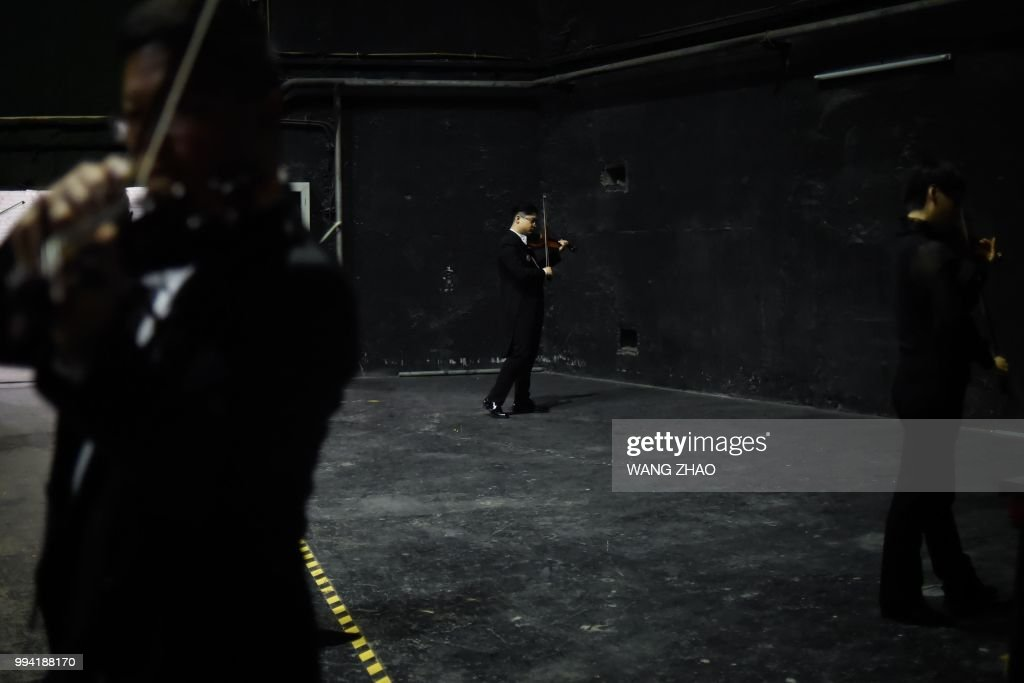 This photo taken on October 14, 2017 shows musicians preparing backstage before a symphonic concert at a theatre in Beijing. - After long relying on Western conductors, a growing number of symphony orchestras around China are now entrusting the baton to a fresh generation of Chinese leaders. (Photo by WANG Zhao / AFP) / TO GO WITH China-music, FEATURE by Julien Girault