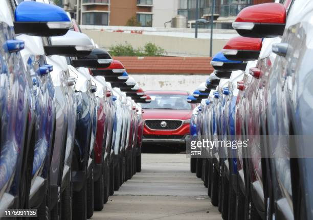This photo taken on October 14, 2019 shows Chinese-made cars waiting to be loaded on a ship for export, in Lianyungang, in China's eastern Jiangsu...