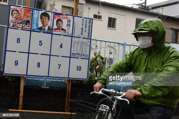 This photo taken on October 19 2017 shows a man cycling past an election poster bulletin board for the upcoming October 22 general election in...