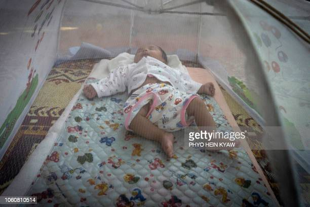 This photo taken on October 19 2018 shows a baby of an unmarried woman sleeping under netting protecting it from mosquitoes at the Myint Mo Myittar...