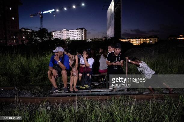 This photo taken on October 19 2018 shows a trolley boy pushing a homemade cart with passengers on a train track in Manila Scores of commuters in the...