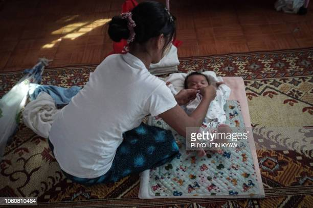 This photo taken on October 19 2018 shows an unmarried woman seeking refuge at the Myint Mo Myittar Single Mothers' Foundation in Yangon preparing...