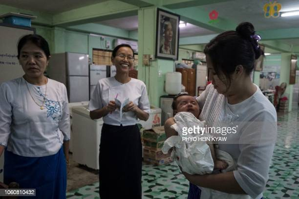 This photo taken on October 19 2018 shows personnel of Myanmar's Social Welfare Department taking care of a baby who was recently handed over to the...