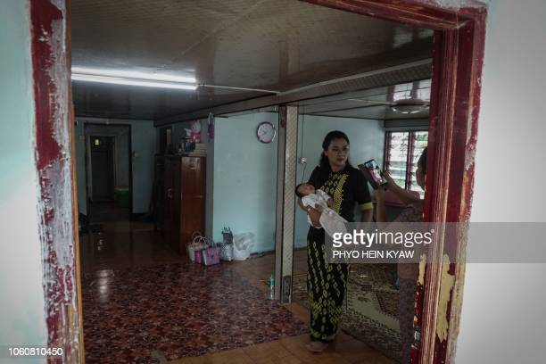This photo taken on October 19 2018 shows radiologist Myat Sandar Thant carrying a baby at the Myint Mo Myittar Single Mothers' Foundation in Yangon...