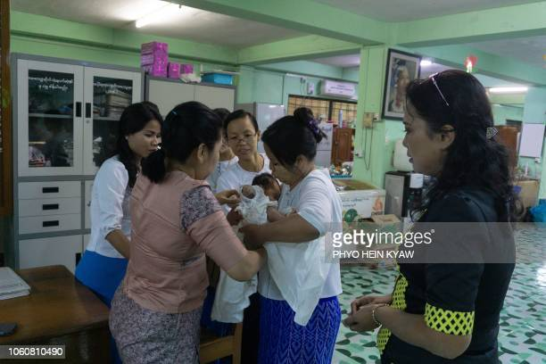 This photo taken on October 19 2018 shows radiologist Myat Sandar Thant looking at a baby she handed over to personnel of the Social Welfare...
