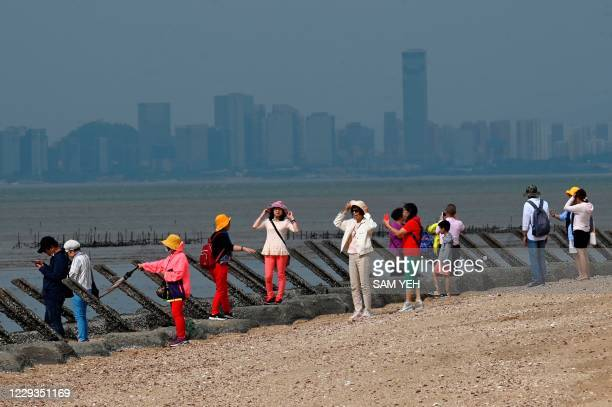 This photo taken on October 20, 2020 shows tourists posing for photos next to anti-landing spikes placed along the coast of Taiwan's Kinmen islands,...