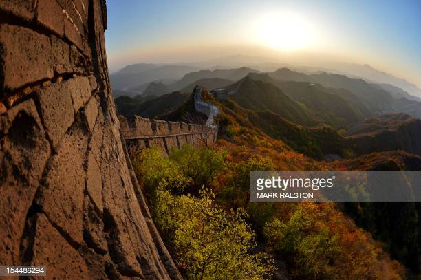 This photo taken on October 20 shows the sun setting over the autumn colours of a section of the Great Wall of China at Jinshanling, Hebei Province....