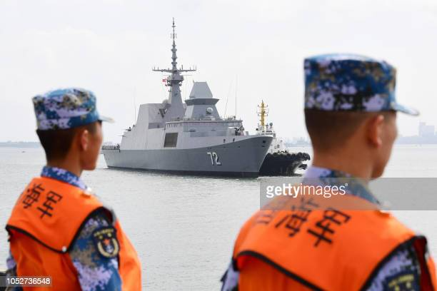 This photo taken on October 21, 2018 shows Chinese sailors watching as a Singapore navy ship arrives at a military port in Zhanjiang, in China's...