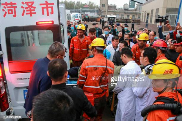 This photo taken on October 21 2018 shows rescuers and medical staffs transferring an injured miner after a mining accident in Yuncheng County in...