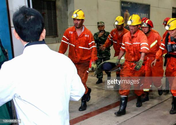 This photo taken on October 21 2018 shows rescuers transferring an injured miner after a mining accident in Yuncheng County in China's eastern...