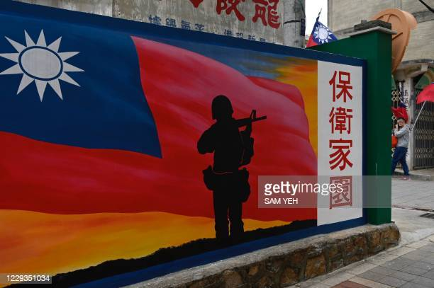 This photo taken on October 21, 2020 shows a tourist walking past a mural painted on a wall on Taiwan's Kinmen islands, which lie just 3.2 kms from...