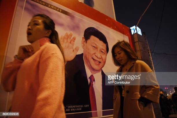 This photo taken on October 24 2017 shows women walking past a roadside poster of Chinese President Xi Jinping after the closing of the 19th...