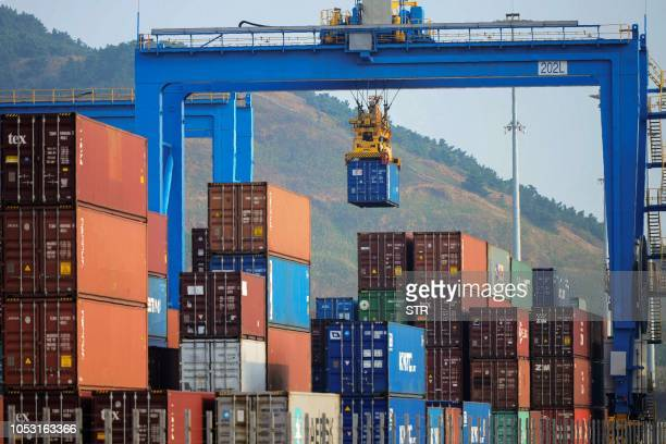 This photo taken on October 24 2018 shows a crane loading and lifting containers at an automated cargo wharf in Qingdao in China's eastern Shandong...