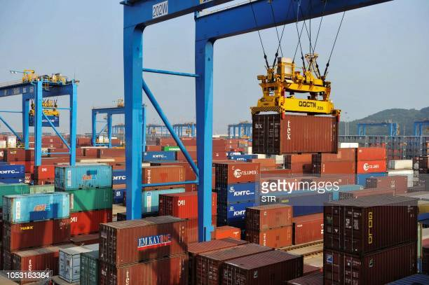 This photo taken on October 24 2018 shows cranes loading and lifting containers at an automated cargo wharf in Qingdao in China's eastern Shandong...