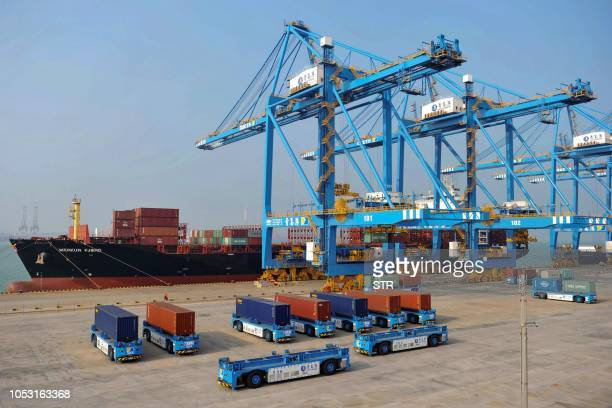 This photo taken on October 24 2018 shows driverless trucks transferring containers at an automated cargo wharf in Qingdao in China's eastern...
