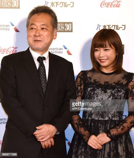 This photo taken on October 25 2017 shows Takahisa Zeze director of 'The Lowlife' posing with original author Mana Sakura in a photo session prior to...