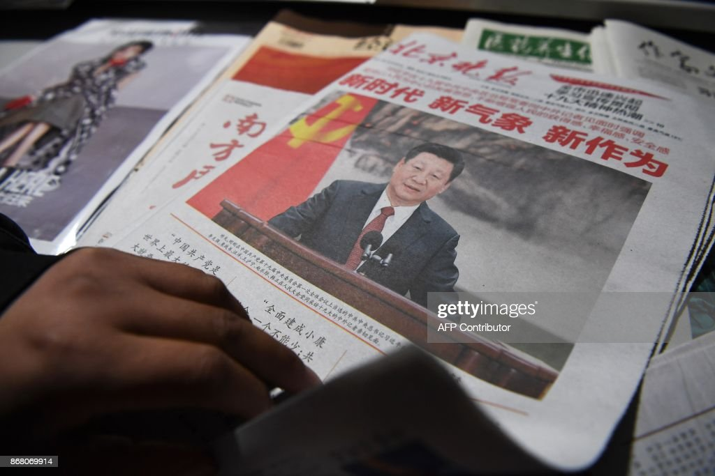 This photo taken on October 26, 2017 shows a newspaper featuring Chinese President Xi Jinping at a news stand a day after Xi introduced China's new Politburo Standing Committee, the nation's top de...