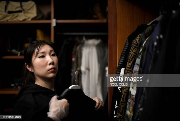 This photo taken on October 26 shows a home organiser arranging the luxury wardrobe of client Chen Rui in Beijing. - China's breakneck growth over...