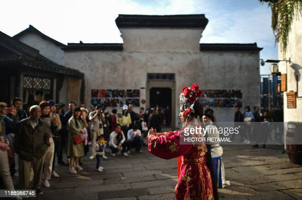 This photo taken on October 28, 2019 shows people watching a Beijing Opera performance during the 7th annual Wuzhen Theatre Festival in Wuzhen in...