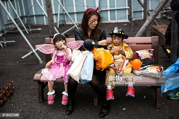 This photo taken on October 29 2016 shows a woman giving snacks to children in costumes during a Halloween parade in Tokyo Tokyo nursed a giant...