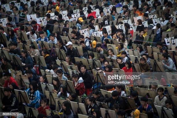 This photo taken on October 29 2017 shows students drawing during a simulation of college entrance exam for art major at Hubei University in Wuhan in...