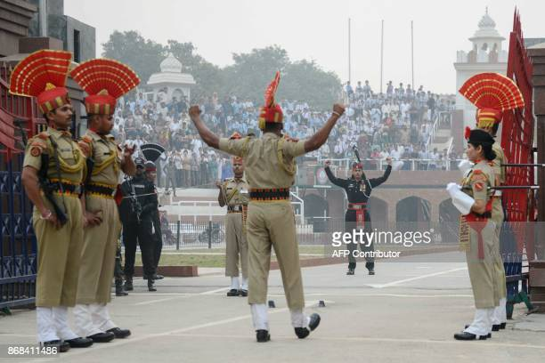 TOPSHOT This photo taken on October 30 2017 shows Indian Border Security Force personnel and Pakistani rangers taking part in the daily beating of...