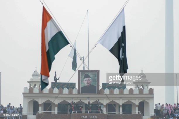 This photo taken on October 30 2017 shows Pakistani rangers saluting under the Indian and Pakistan flags during the daily beating of the retreat...