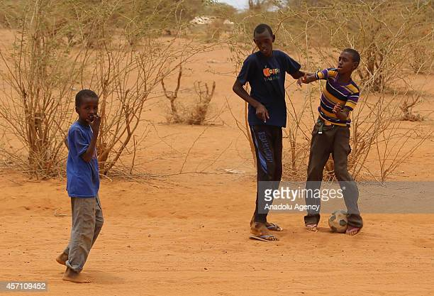 This photo taken on October 4 2014 shows three refugee boys playing soccer at Dadaab refugee camp in Kenya the largest refugee complex in the world...