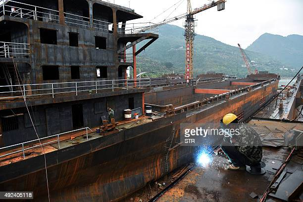 This photo taken on October 4 2015 shows a worker welding a part of a cargo ship in a shipyard in China's southwest Chongqing municipality Chinese...