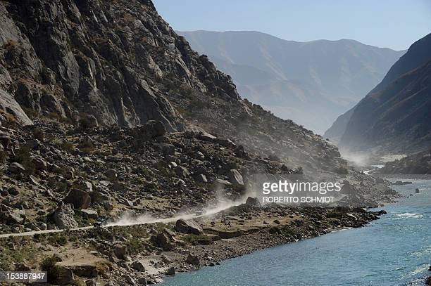 This photo taken on October 6 2012 shows two pickup trucks making their way west on the main road connecting the capital of Faizabad in the province...