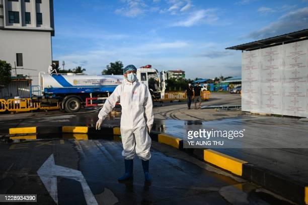 This photo taken on October 6 2020 shows a volunteer personal protective equipment cleaning the frontage of Myanmar Expo Hall converted as Happy...