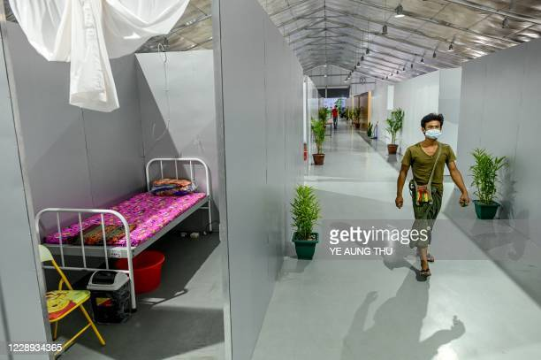 This photo taken on October 6 2020 shows a worker walking inside the Myanmar Expo Hall converted as Happy Covid Center for people infected with...