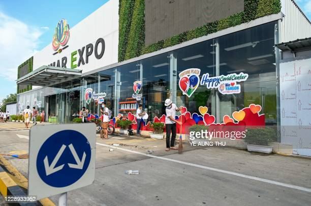 This photo taken on October 6 2020 shows volunteers cleaning the frontage of Myanmar Expo Hall converted as Happy Covid Center for people infected...