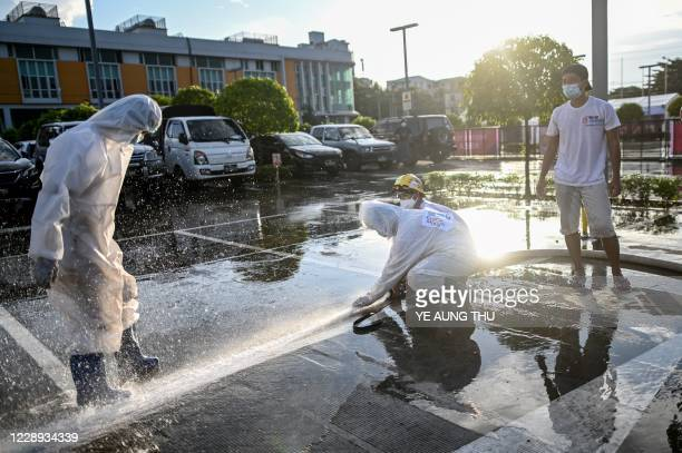 This photo taken on October 6 2020 shows volunteers wearing personal protective equipment cleaning the frontage of Myanmar Expo Hall converted as...