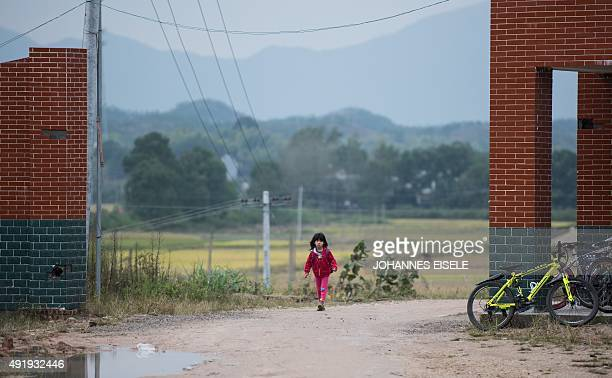 This photo taken on October 8, 2015 shows a schoolgirl walking along the street on her way to the Shiniuzhai Puan Center Primary School in Pingjiang...