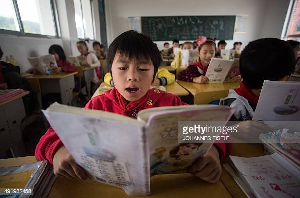 This photo taken on October 8 2015 shows Chinese schoolchildren attending class at the Shiniuzhai Puan Center Primary School in Pingjiang County in...