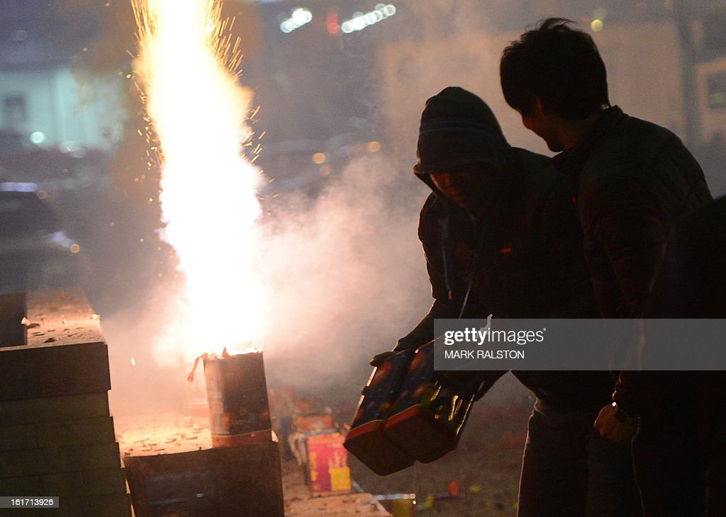 This photo taken on on February 14, 2013 shows Chinese traders letting off fireworks to acknowledge the 'god of wealth' outside the Silk Market and bring their businesses prosperity and good fortun...