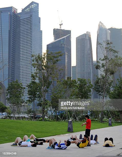 This photo taken on September 10 2012 shows people exercising after work at a park in downtown Singapore The number of foreign workers in Singapore...
