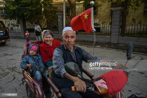 This photo taken on September 11 2019 shows a man driving a vehicle in an ethnic Uighur neighborhood in Aksu in the region of Xinjiang